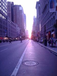 view of sun setting between buildings in midtown Manhattan